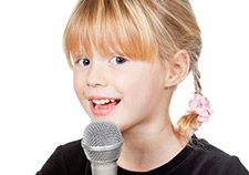Image of a child singing into a microphone